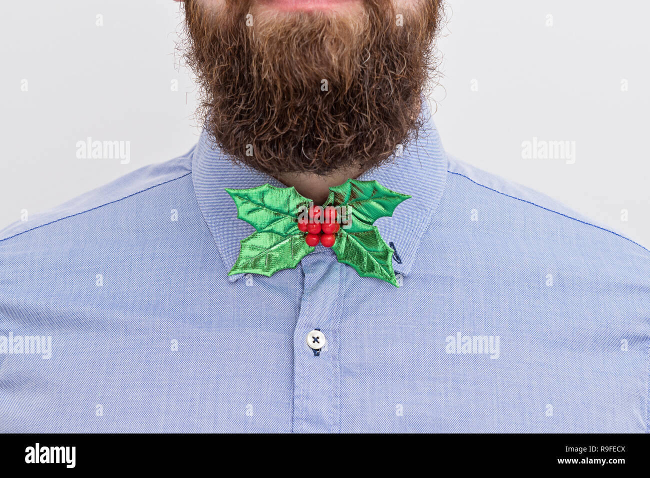 Close up of handsomely bearded office manager hipster with festive formal wear Christmas bow tie and blue shirt on white background. Christmas corpora Stock Photo