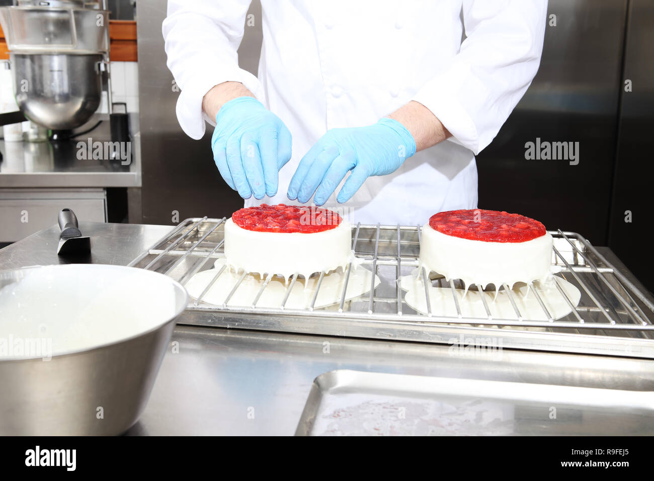 hands pastry chef prepares a cake, cover with icing and decorate with strawberries, works on a stainless steel industrial kitchen work top - Stock Image