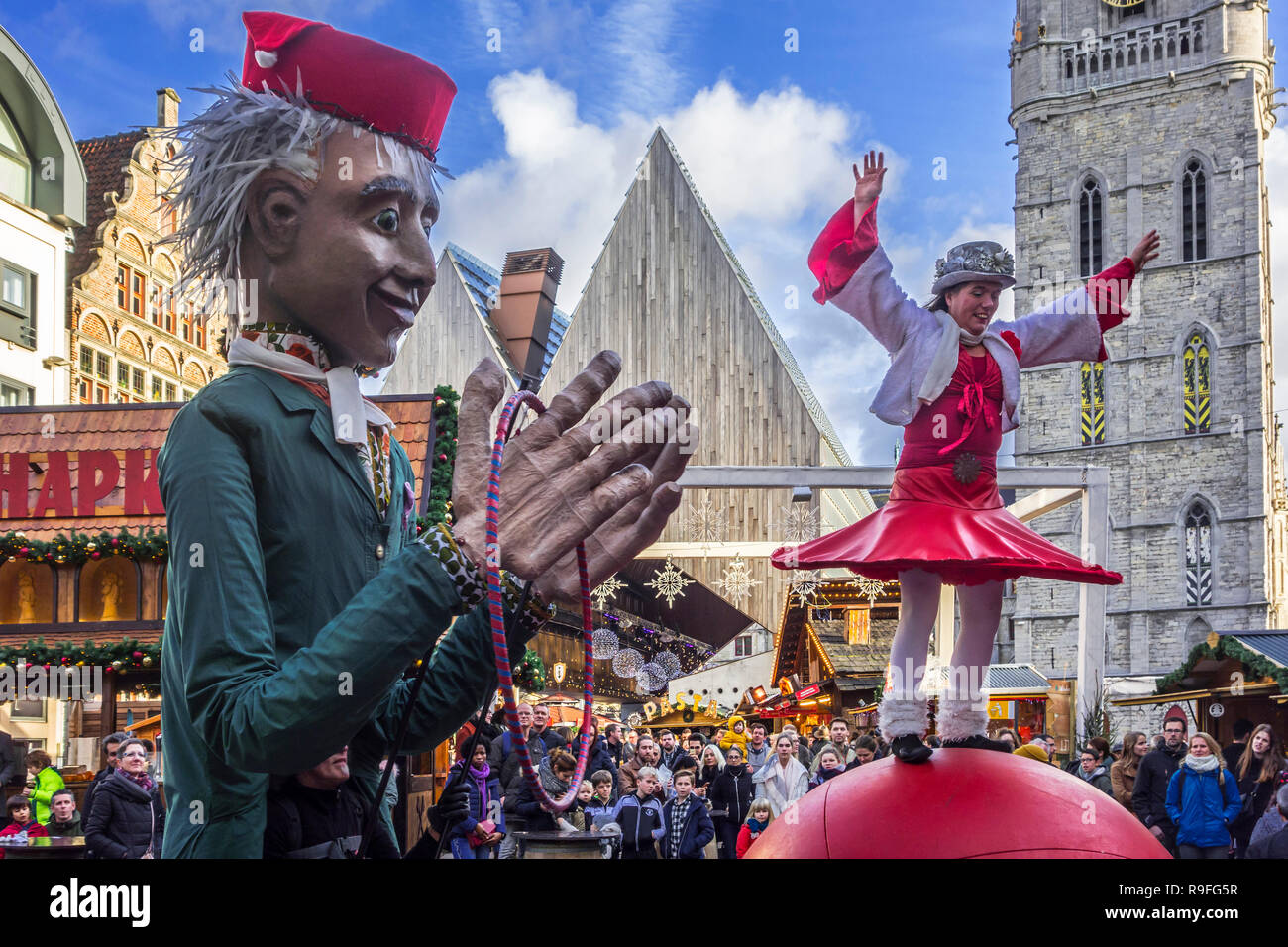 Puppeteer and street performer performing balancing act on giant ball during Christmas market in winter in Ghent, Flanders, Belgium - Stock Image