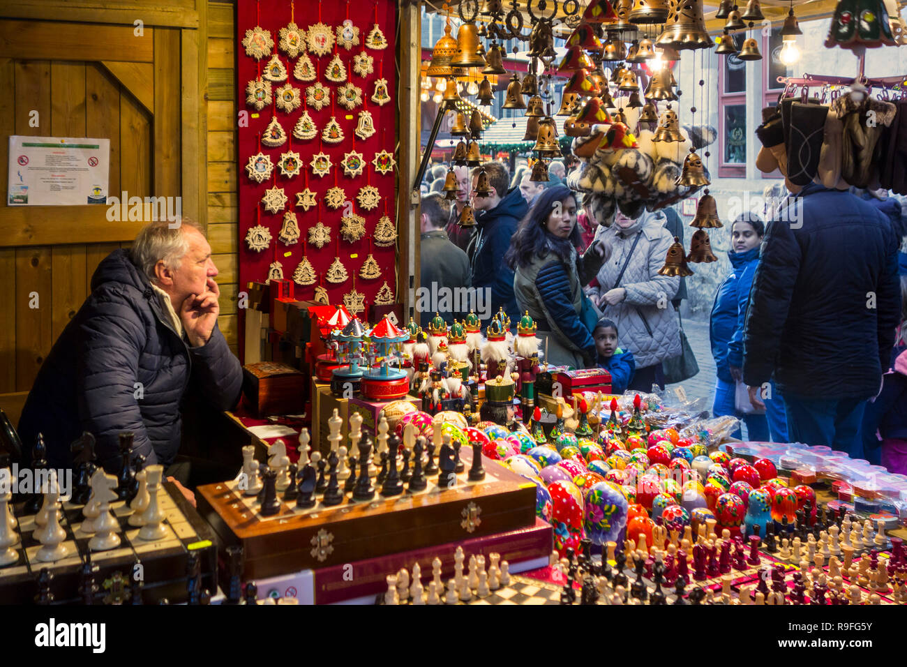 Street vendor in booth selling Xmas presents at Christmas market in winter in the city Ghent, Flanders, Belgium - Stock Image