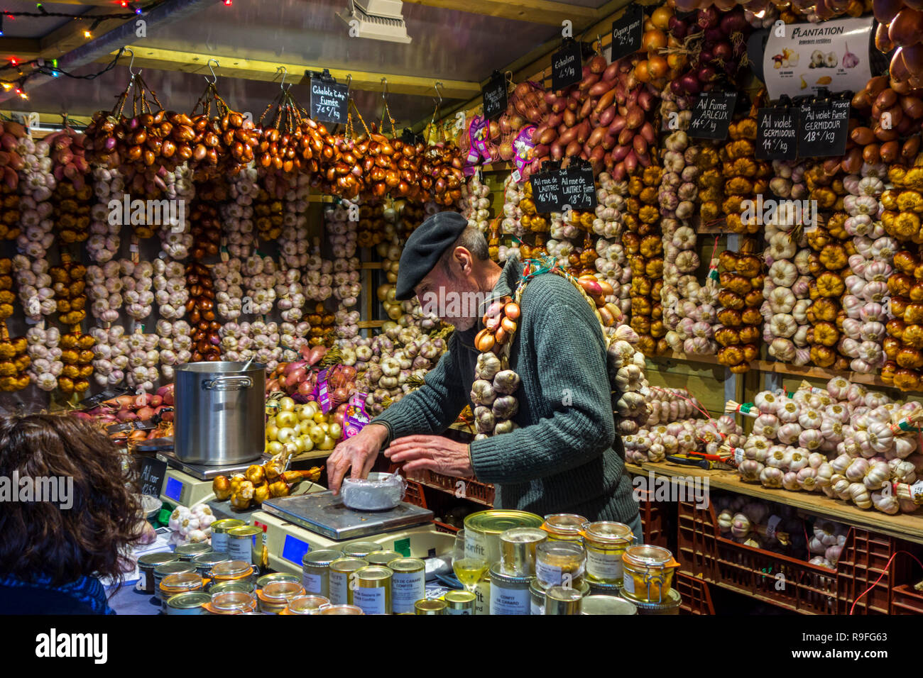 Frenchman / street vendor in booth selling garlic and French food specialities / regional products at Christmas market in winter - Stock Image