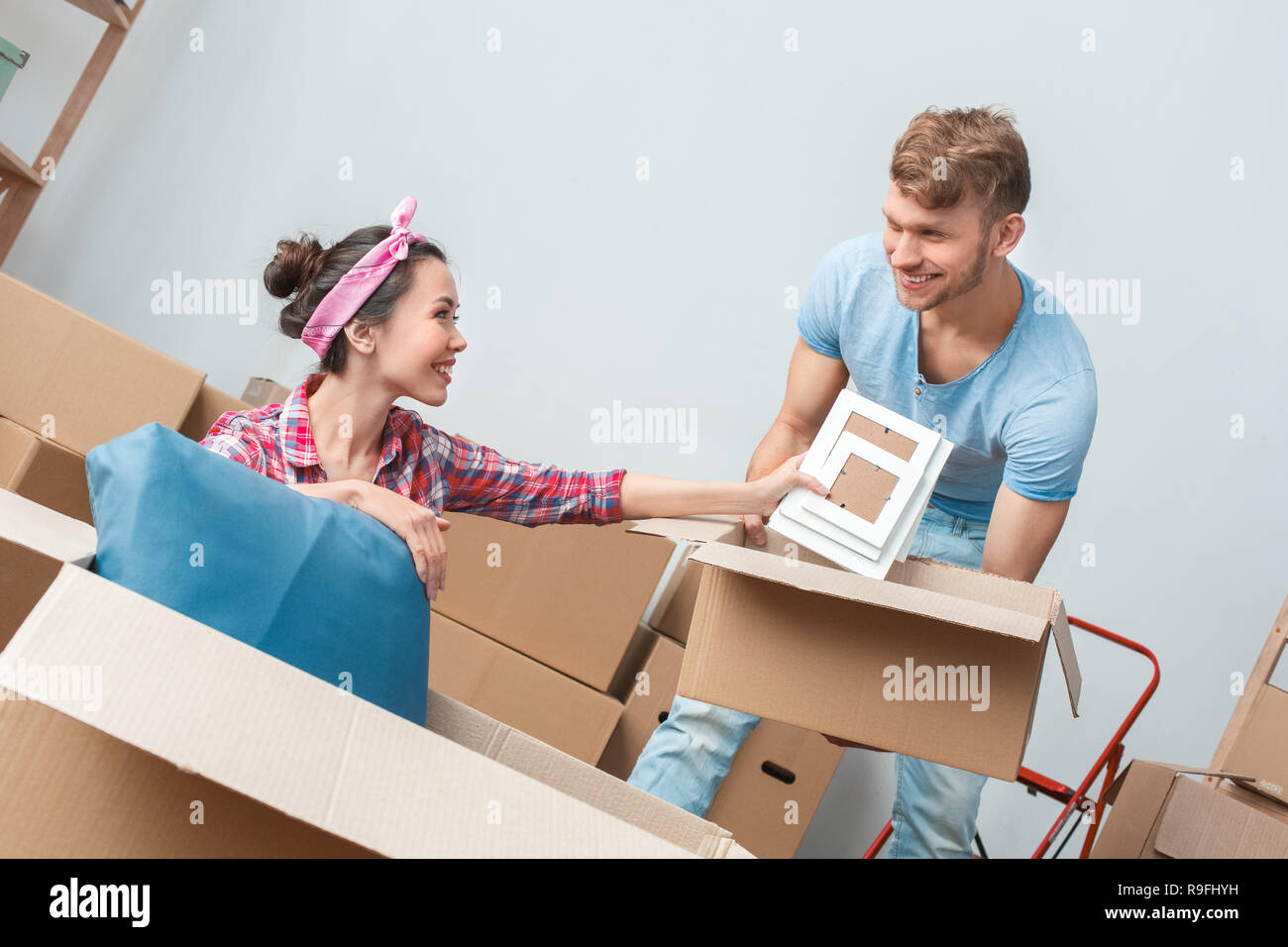 Young Husband And Wife Moving To New Place Packing Things Woman