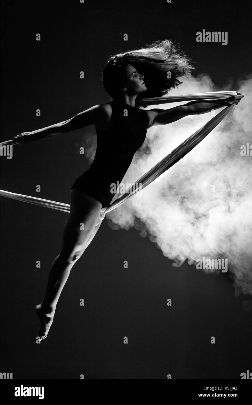 female posing aerial anti-gravity yoga on a hammock with smoke in the background - Stock Image