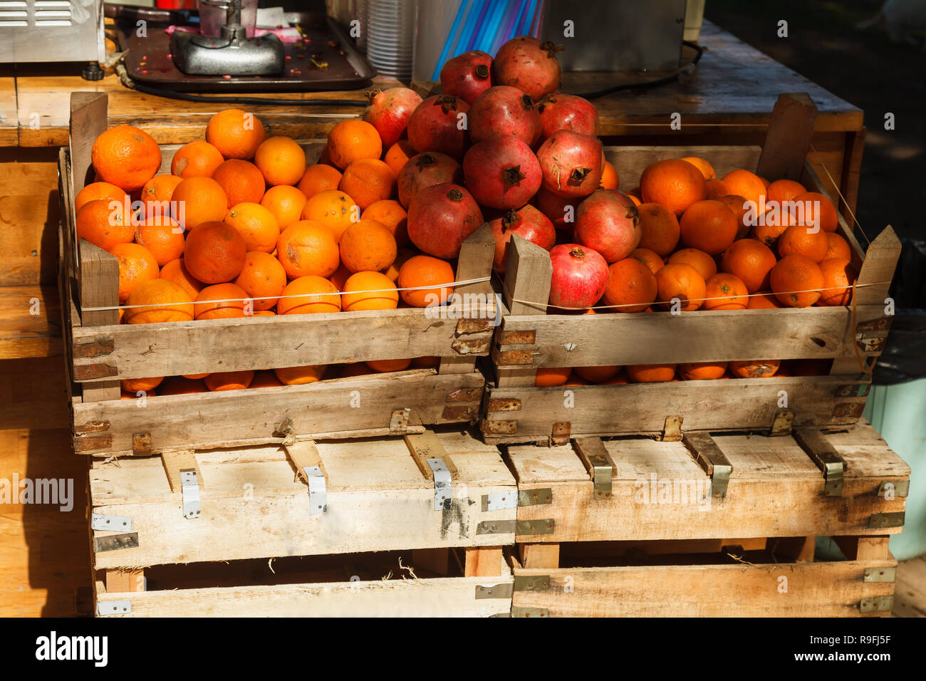 Boxes full of oranges and pomegranates are sold on the market. Street trade in fresh fruit. - Stock Image