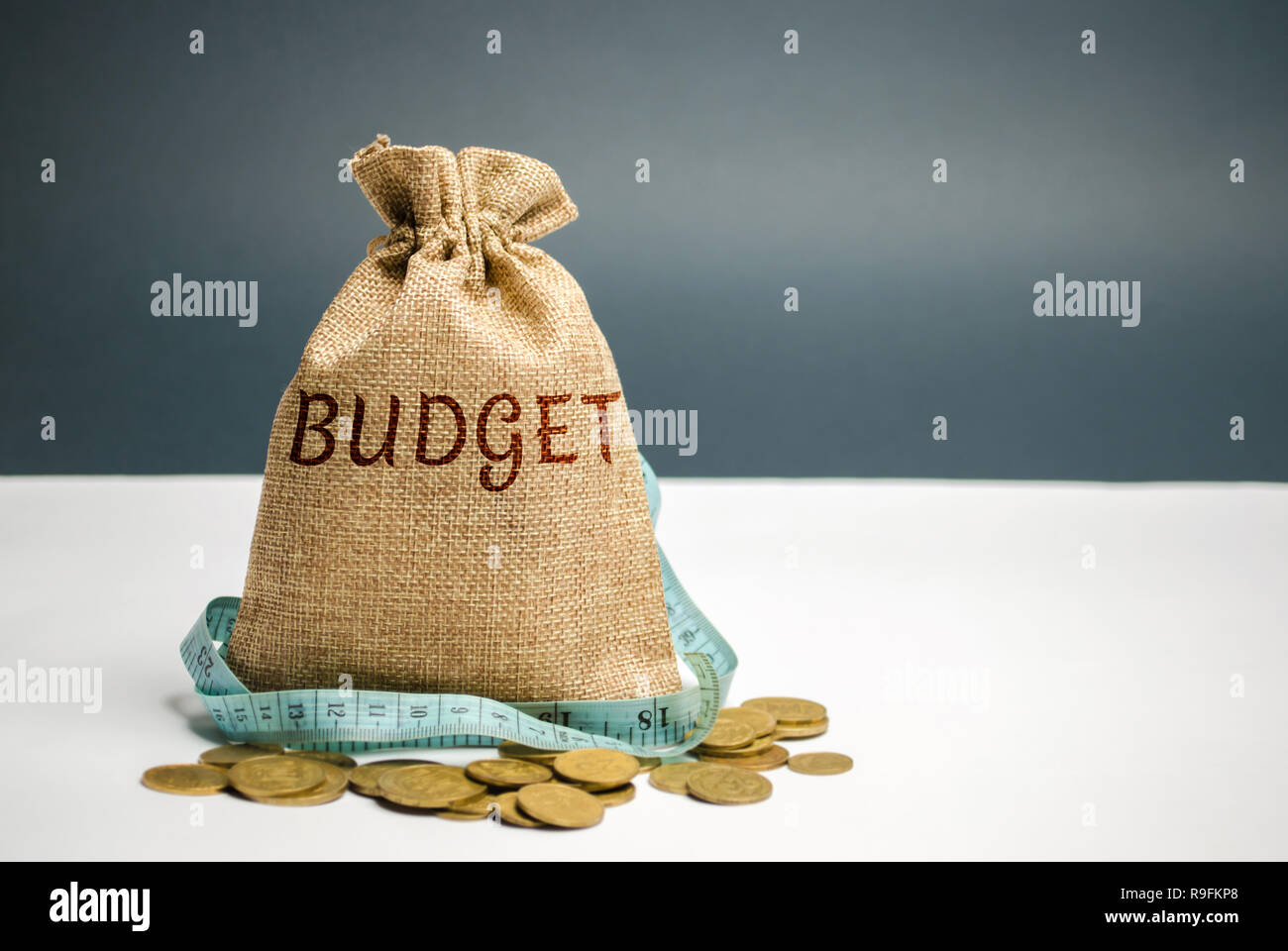 Bag with money and tape measure and the word budget. Limited budget. Lack of money. The concept of accumulating money in the family budget. Family Ins Stock Photo
