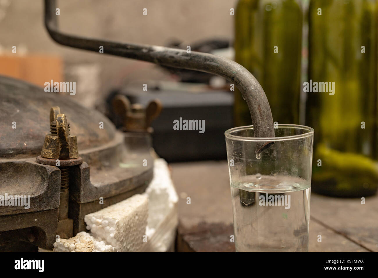 Alcohol production in home conditions. Accessories for the production of homemade moonshine. Place - home basement. - Stock Image