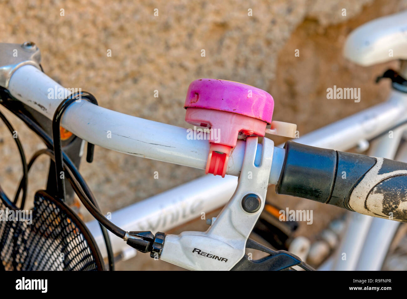 Pink bell on bicycle handlebars - Stock Image