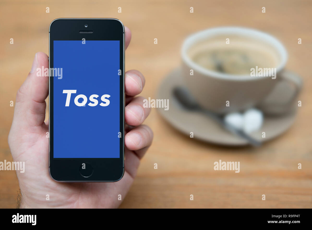 A man looks at his iPhone which displays the Toss logo (Editorial use only). - Stock Image