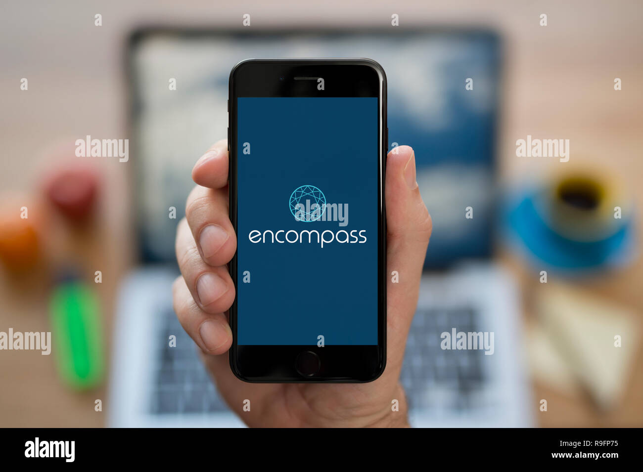 A man looks at his iPhone which displays the Encompass Corporation logo (Editorial use only). - Stock Image