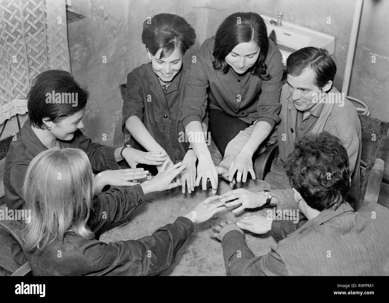 A group of young adults appear to play a parlor game or participate in a seance, ca. 1955. - Stock Image