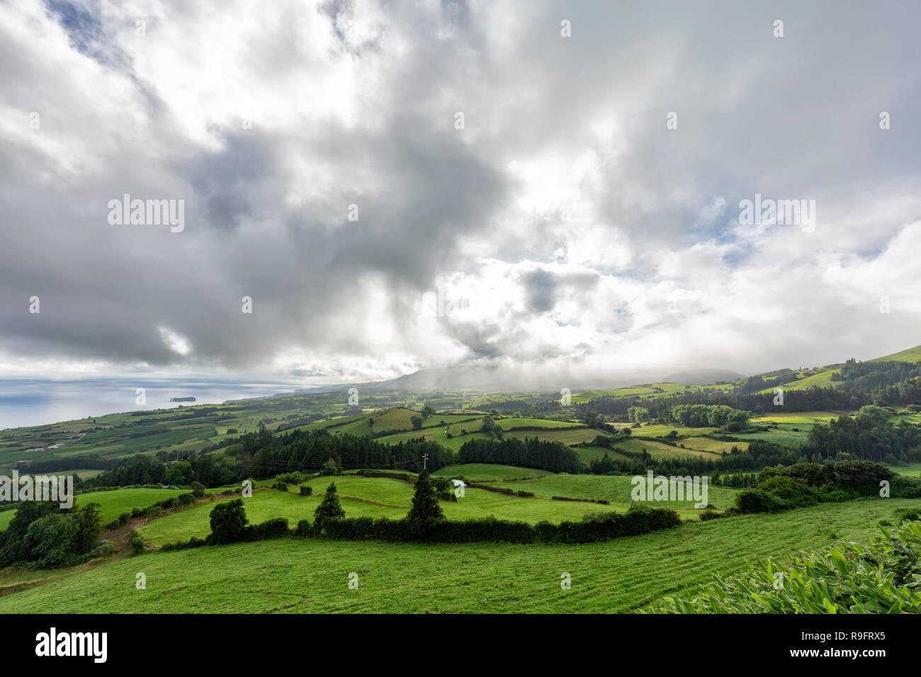 Pastures with beautiful clouds in the summertime near Vila Franca do Campo in the Azores, Portugal. - Stock Image