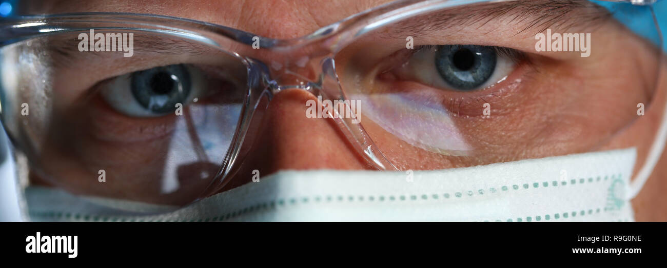 Handsome male physician face wearing protective mask - Stock Image