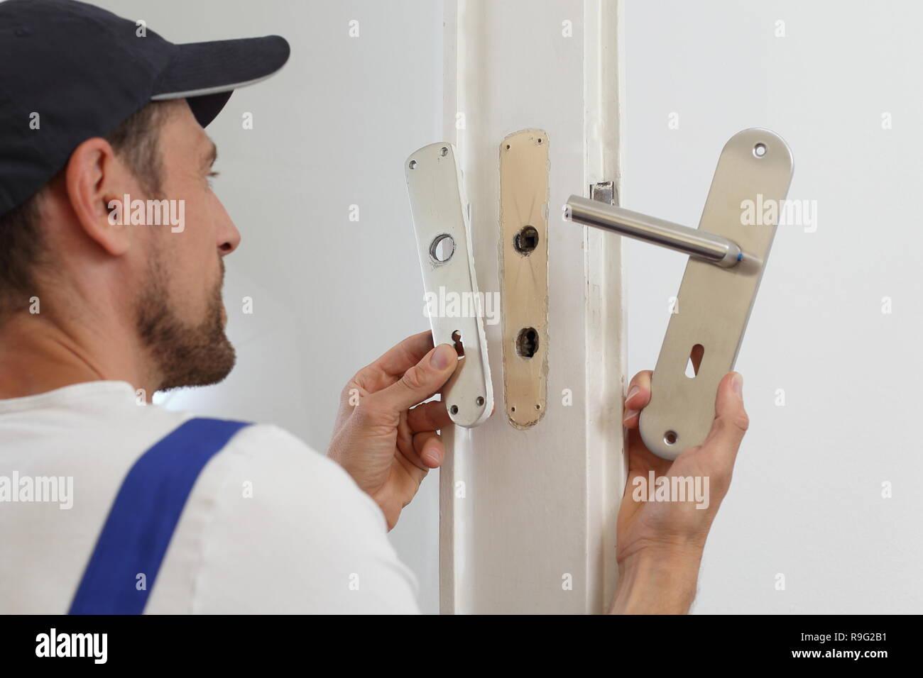 A man Replacing a door handle - Stock Image