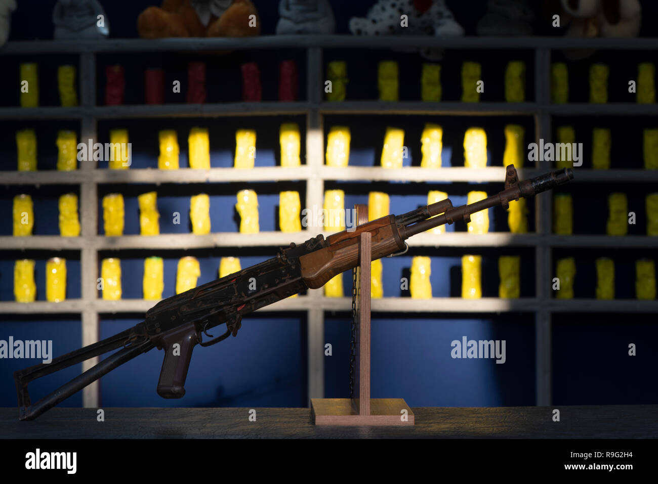 shooting gallery, air gun in the foreground. in the background, the banks are dented from the shots. on top of toys as prizes. - Stock Image