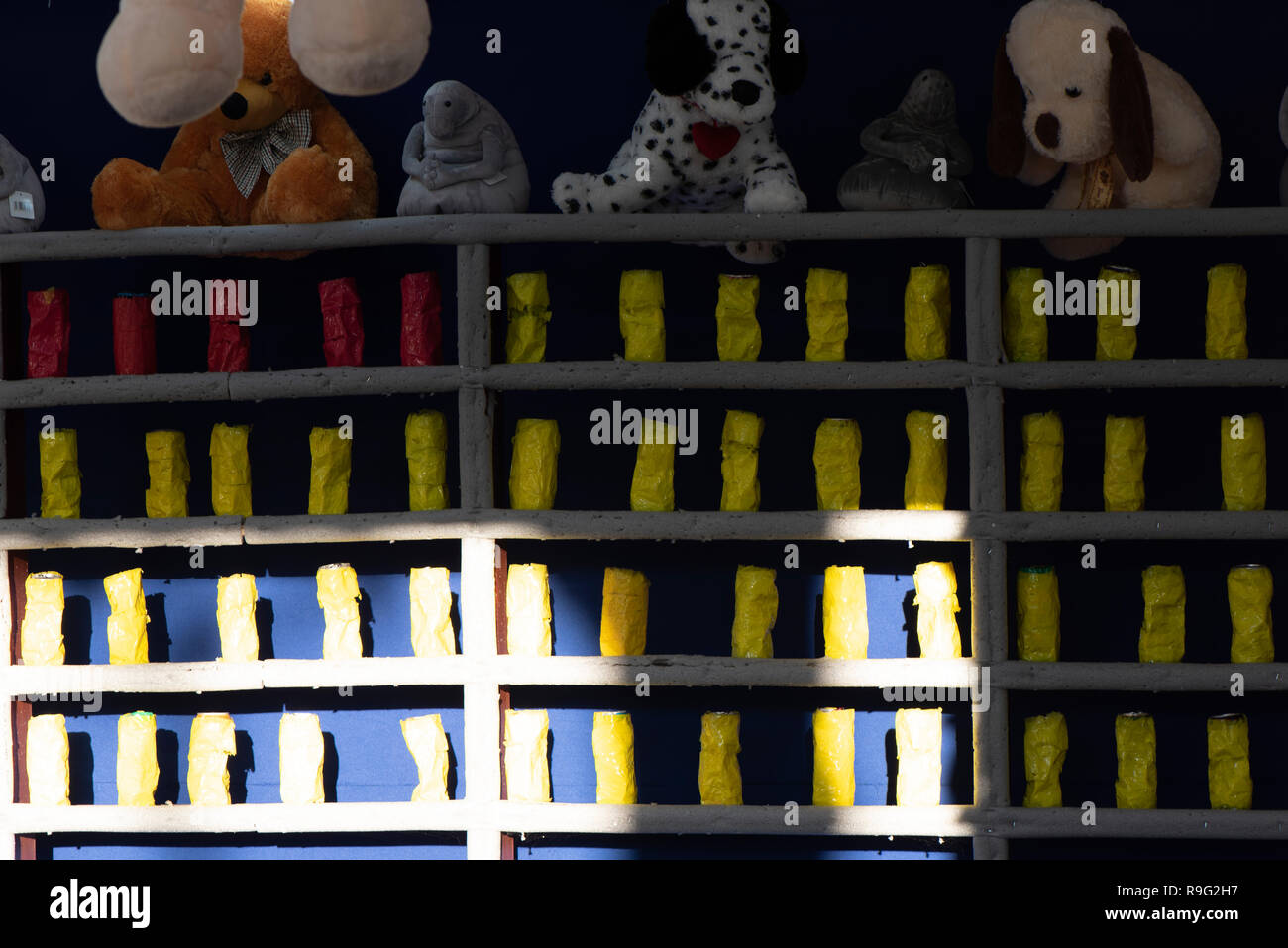 shooting gallery with yellow cans and prize toys - Stock Image