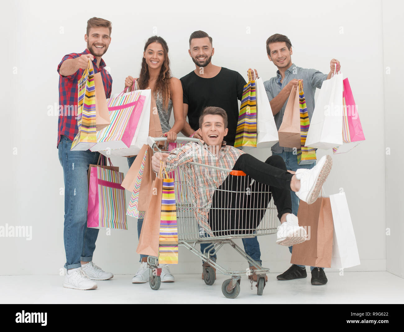 happy group of young people with shopping bags - Stock Image
