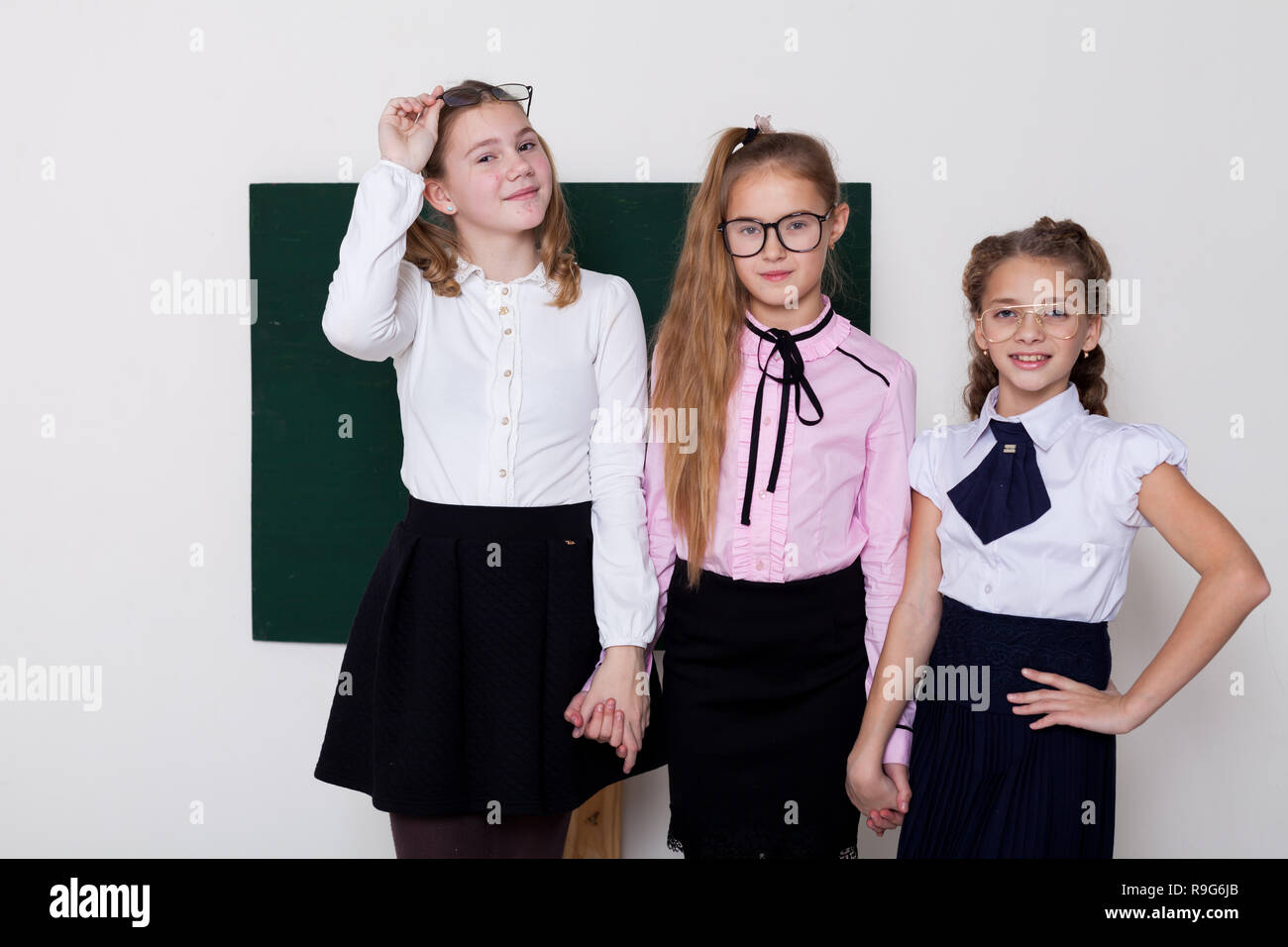 three girls in glasses at the Blackboard in a class lesson - Stock Image