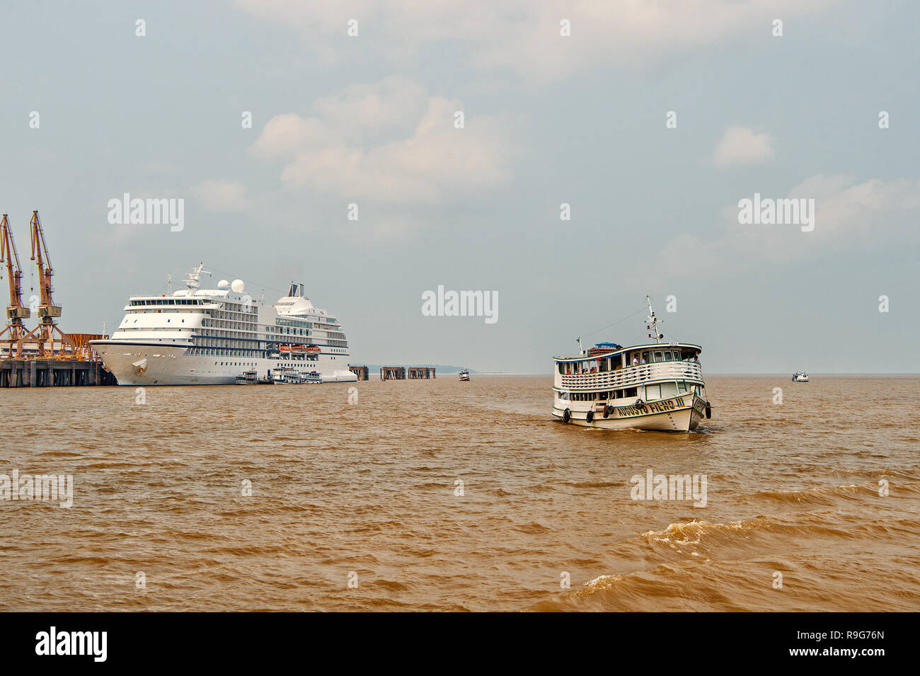 Santarem, Brazil - December 02, 2015: luxury lifestyle concept. Ship floating on sea and Seven Seas Navigator cruise liner in dock on grey sky background. Tourist destination and travelling - Stock Image