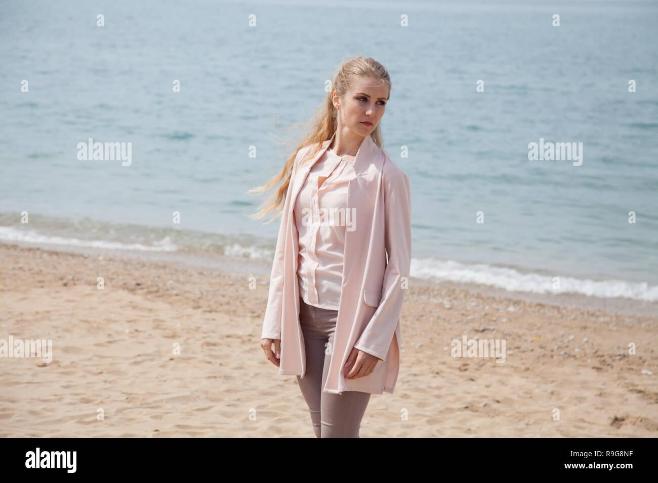 beautiful blonde woman walking on the sandy sea-Beach - Stock Image
