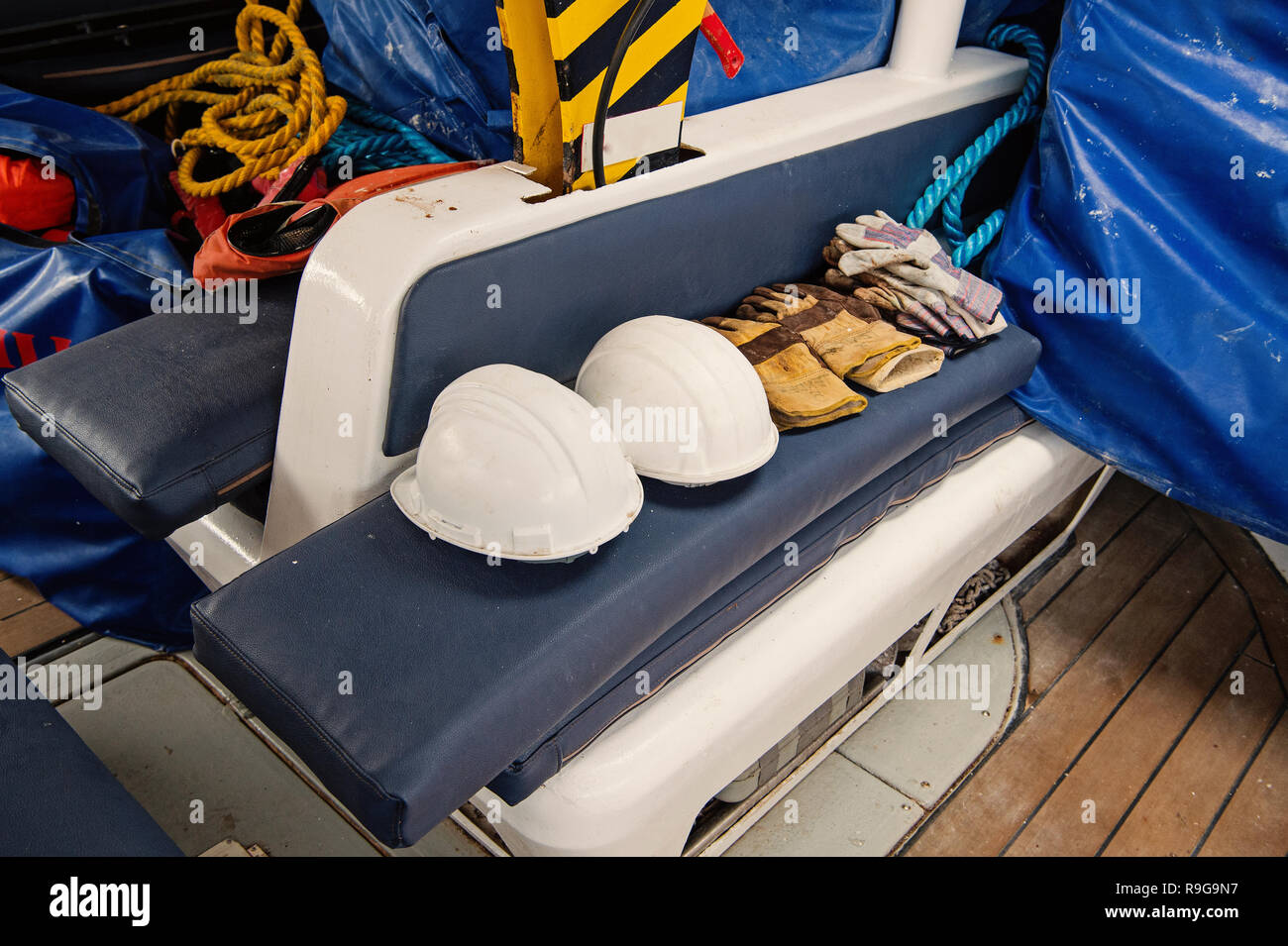 Gloves and helmets on grey seat background in boca de valeria, brazil. Construction, industry, professional workwear and equipment. Safety and protection concept. - Stock Image