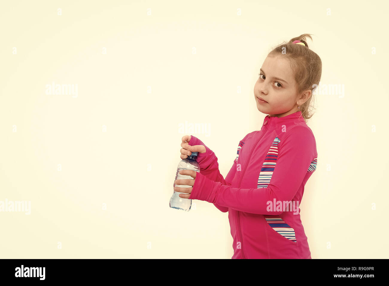 Child feel thirsty in pink suit isolated on white. Girl with bottle of drinking water. Health and healthy drink. Dehydration, thirst concept. Fluid balance, hydration, copy space - Stock Image