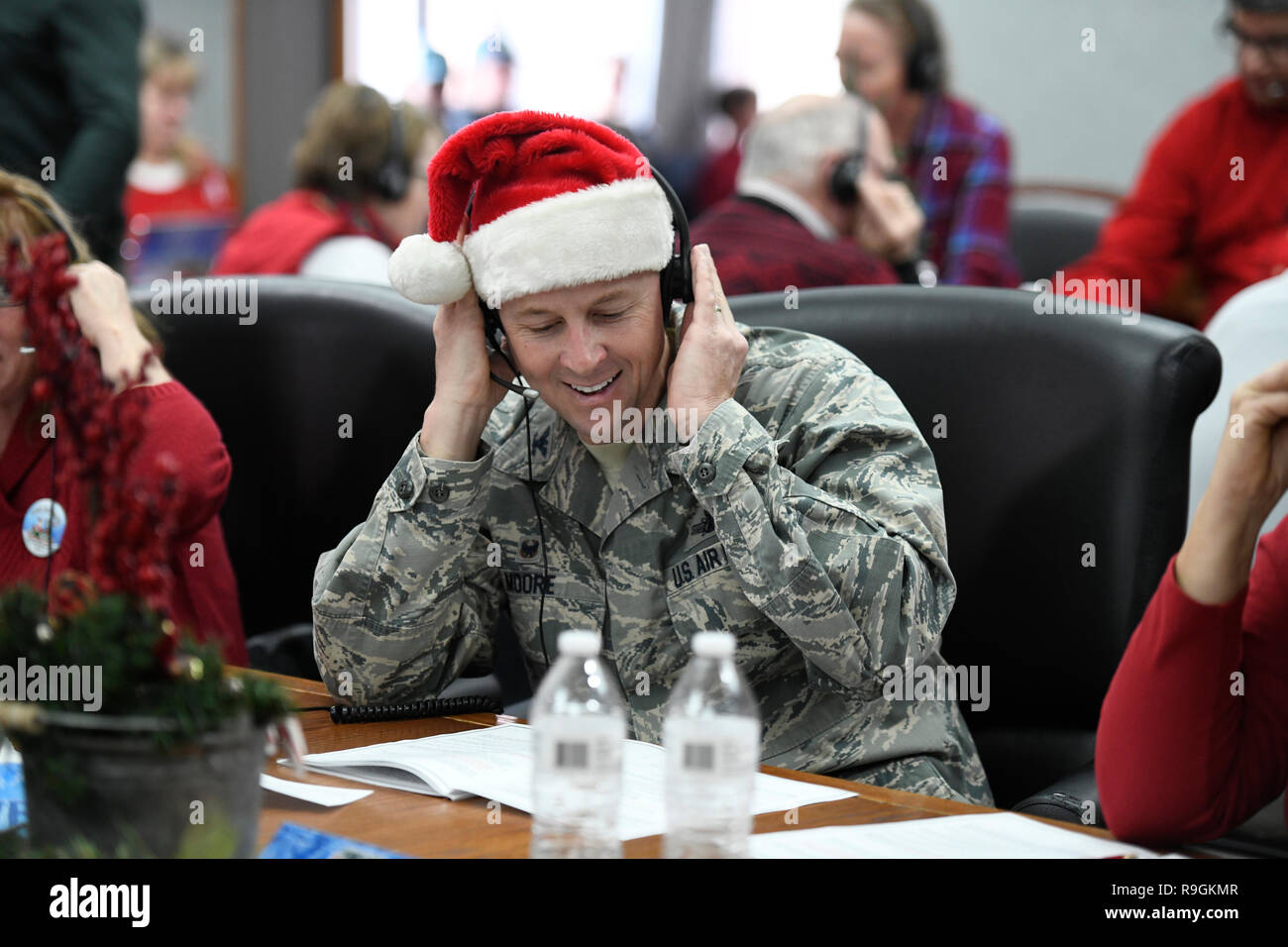Colorado Springs, Colorado, USA. 24th Dec 2018. USAF Col. Todd Moore, 21st Space Wing commander, answers phones and emails from children around the world during the annual NORAD Tracks Santa event at Peterson Air Force Base December 24, 2018 in Colorado Springs, Colorado. Last year NTS had more than 1,600 volunteers answering 125,000 phone calls, 2,000 emails and 7,450 on-star requests from children around the world asking where Santa is at and when will he arrive at their house. Credit: Planetpix/Alamy Live News - Stock Image