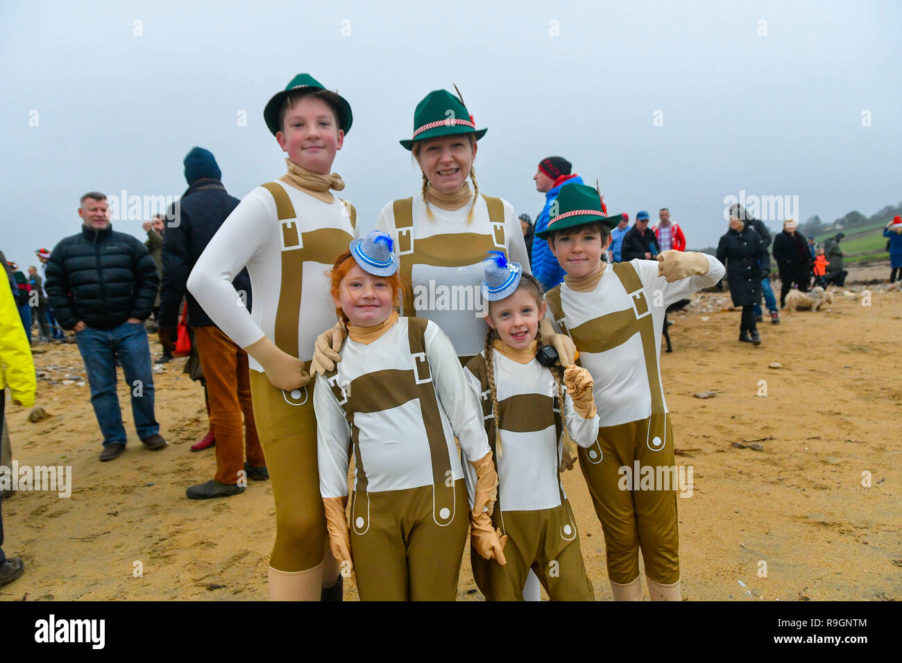 Charmouth, Dorset, UK. 25th Dec, 2018. Christmas day swimmers Jack Straham, Milly Straham (Both visting from Canada) with Nikki, Finn and Darcy McAllister who are all wearing fancy dress before braving the chilly water to take a dip in the sea at Charmouth in Dorset to raise money for the RNLI. Picture Credit: Graham Hunt/Alamy Live News Stock Photo