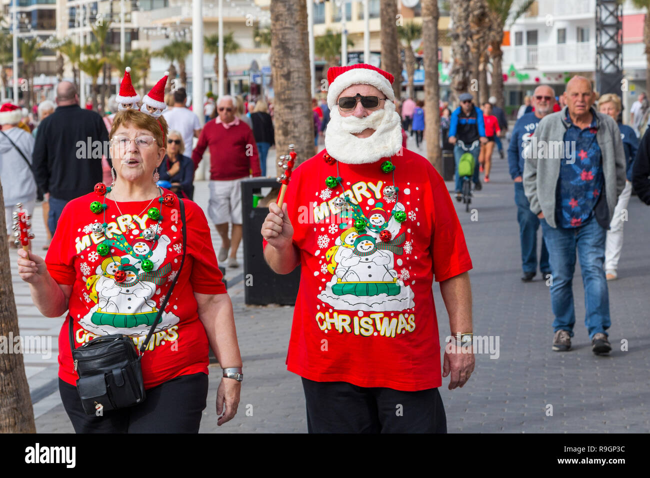 Benidorm, Costa Blanca, Spain, 25th December 2018. British tourists dress for the occasion on Christmas Day in this favourite getaway destination for Brits escaping the cold weather at home. Temperatures will be in the mid to high 20's Celsius today in this mediterranean hotspot. Couple wearing Christmas clothing and santa hats. Middle aged couple wearing bright red Christmas jumpers and hats, with santa beard waliking outside in sun. Stock Photo