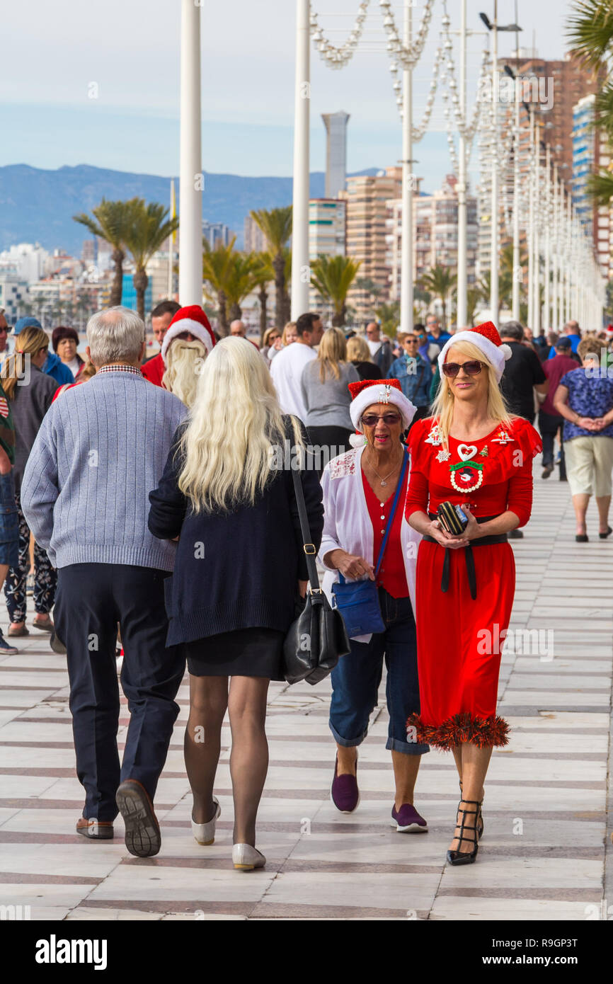 Benidorm, Costa Blanca, Spain, 25th December 2018. British tourists dress for the occasion on Christmas Day in this favourite getaway destination for Brits escaping the cold weather at home. Temperatures will be in the mid to high 20's Celsius today in this mediterranean hotspot. Two women wearing Christmas clothing strolling on Levante beach promenade. Stock Photo