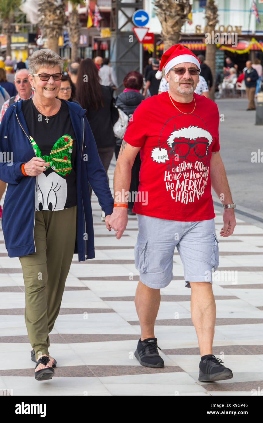 Benidorm, Costa Blanca, Spain, 25th December 2018. British tourists dress for the occasion on Christmas Day in this favourite getaway destination for Brits escaping the cold weather at home. Temperatures will be in the mid to high 20's Celsius today in this mediterranean hotspot. Couple wearing Christmas clothing and santa hats. Stock Photo