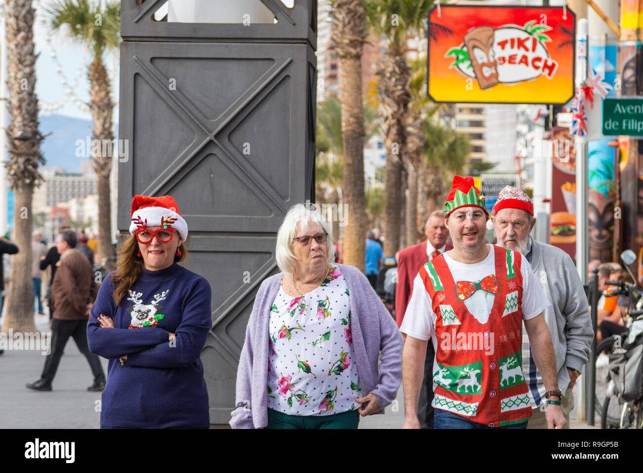 Benidorm, Costa Blanca, Spain, 25th December 2018. British tourists dress for the occasion on Christmas Day in this favourite getaway destination for Brits escaping the cold weather at home. Temperatures will be in the mid to high 20's Celsius today in this mediterranean hotspot.  Middle aged people wearing Christmas jumpers outside in the sun. Stock Photo