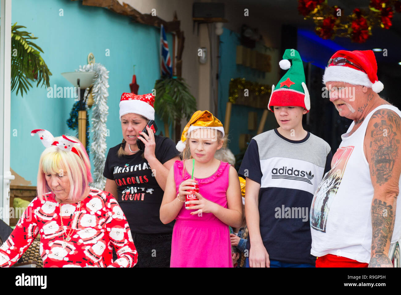 Benidorm, Costa Blanca, Spain, 25th December 2018. British tourists dress for the occasion on Christmas Day in this favourite getaway destination for Brits escaping the cold weather at home. Temperatures will be in the mid to high 20's Celsius today in this mediterranean hotspot. Family with kids outside wearing Christmas clothing and hats. Stock Photo