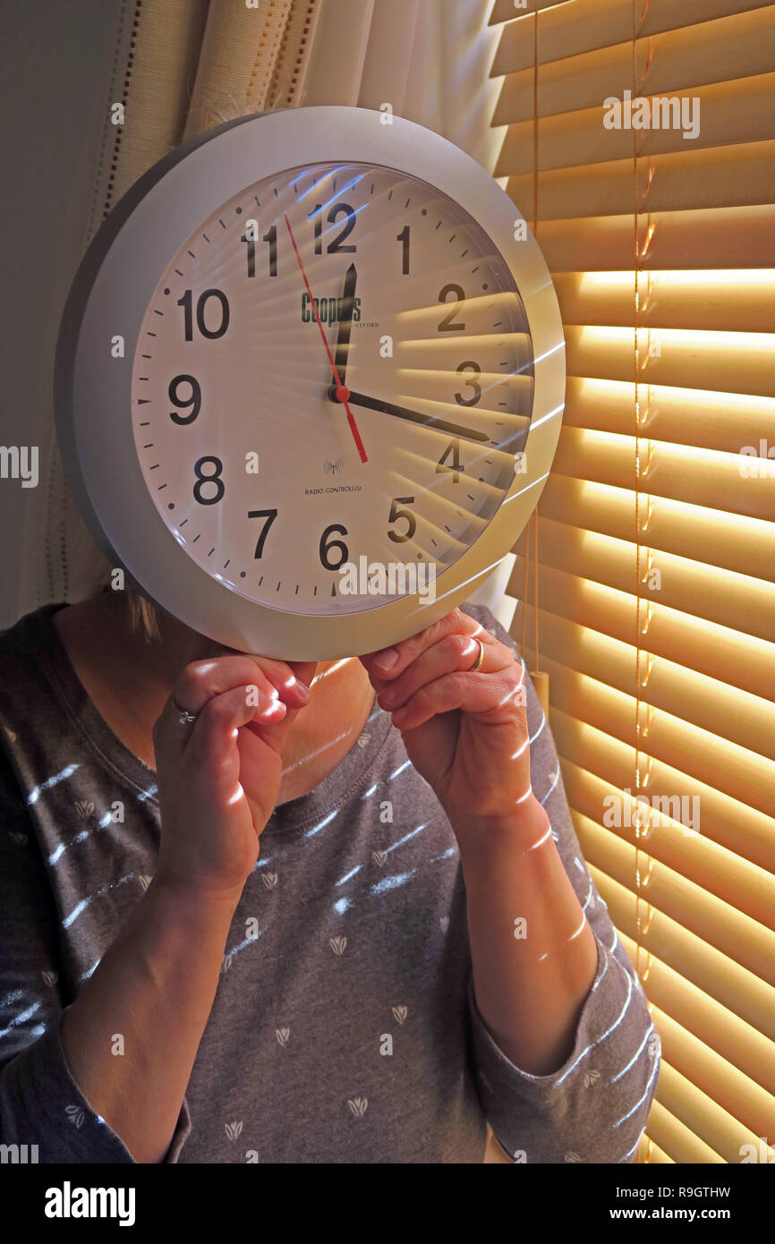 Woman holding a clock face, Daylight Saving Time / British summer Time , clocks going back or forward an hour - Stock Image