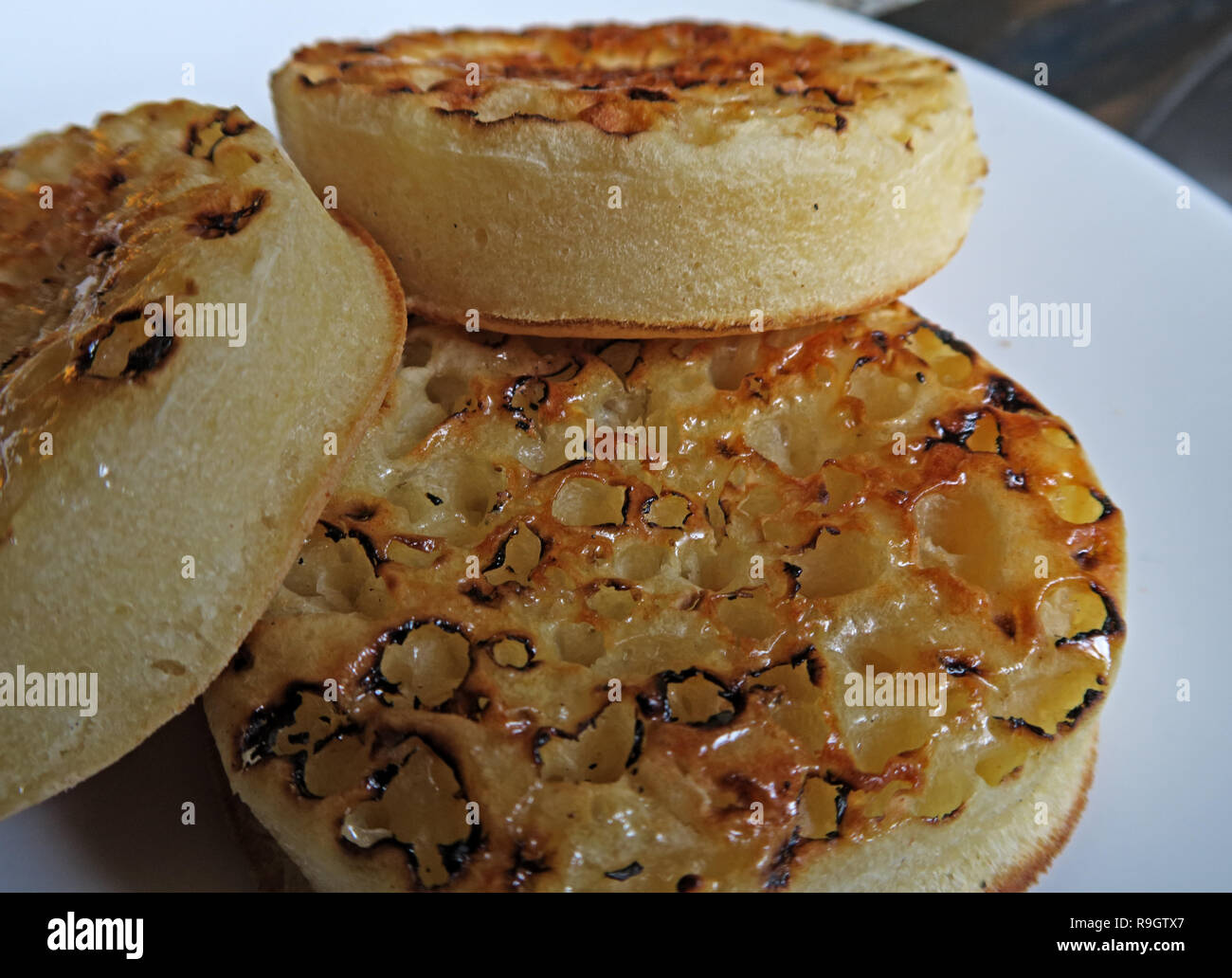 Three toasted buttered English Crumpets on a white plate - Stock Image