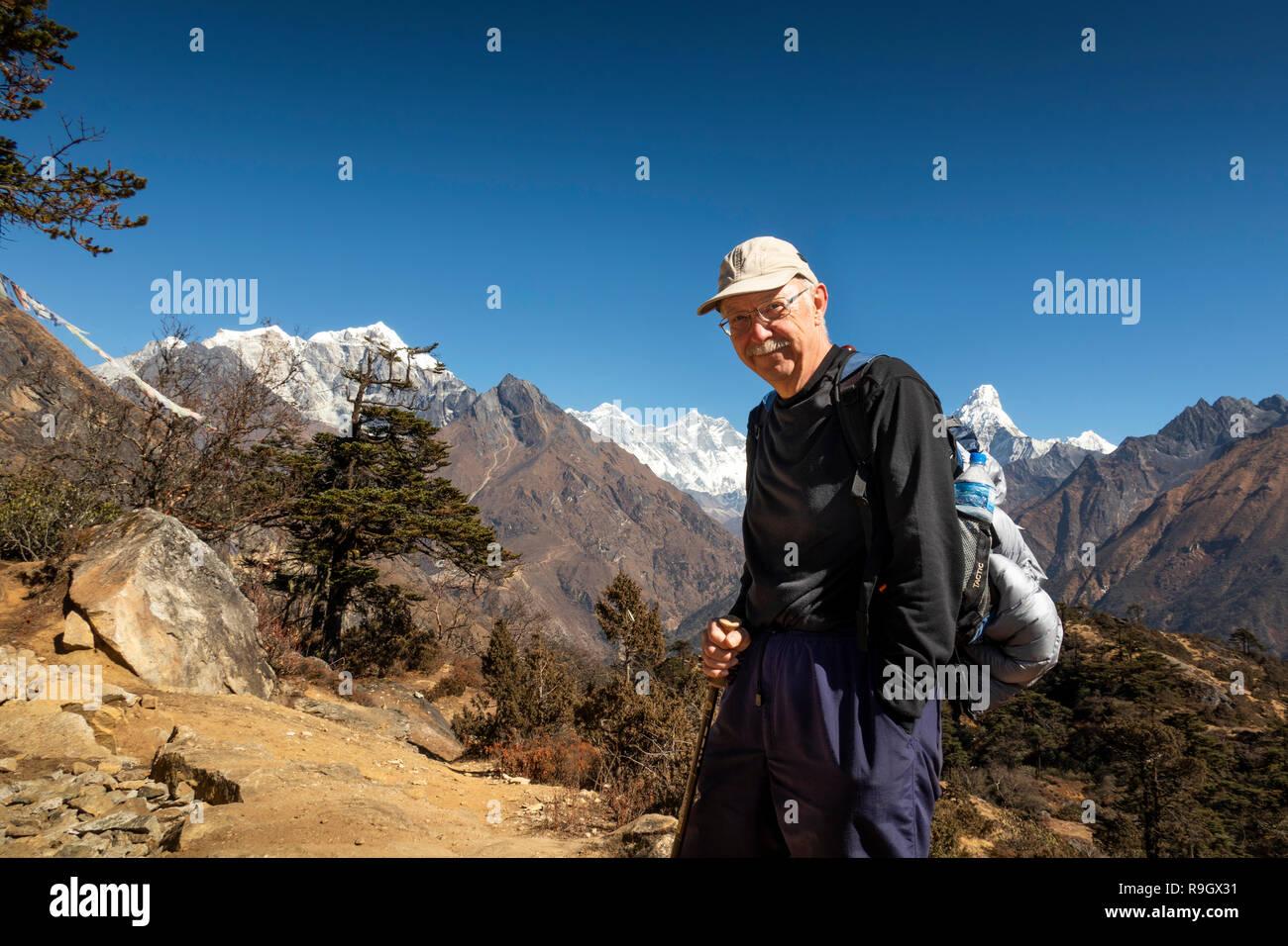Nepal, Everest Base Camp Trek, older male trekker enjoying view of Mount Everest and surrounding Himalayan mountains - Stock Image