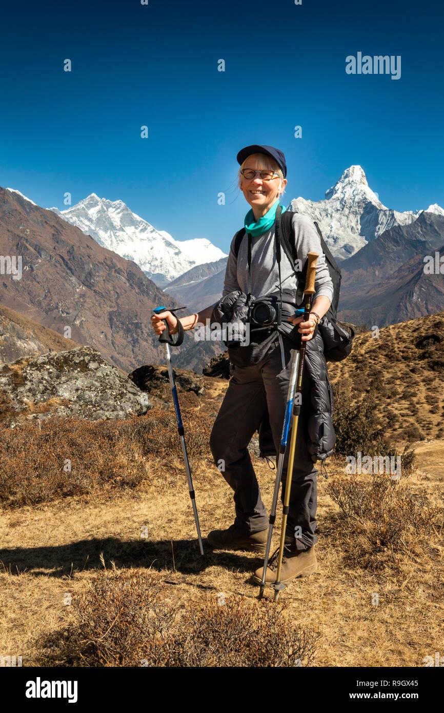 Nepal, Everest Base Camp Trek, senior female trekker with trekking poles amongst Himalayan mountains - Stock Image