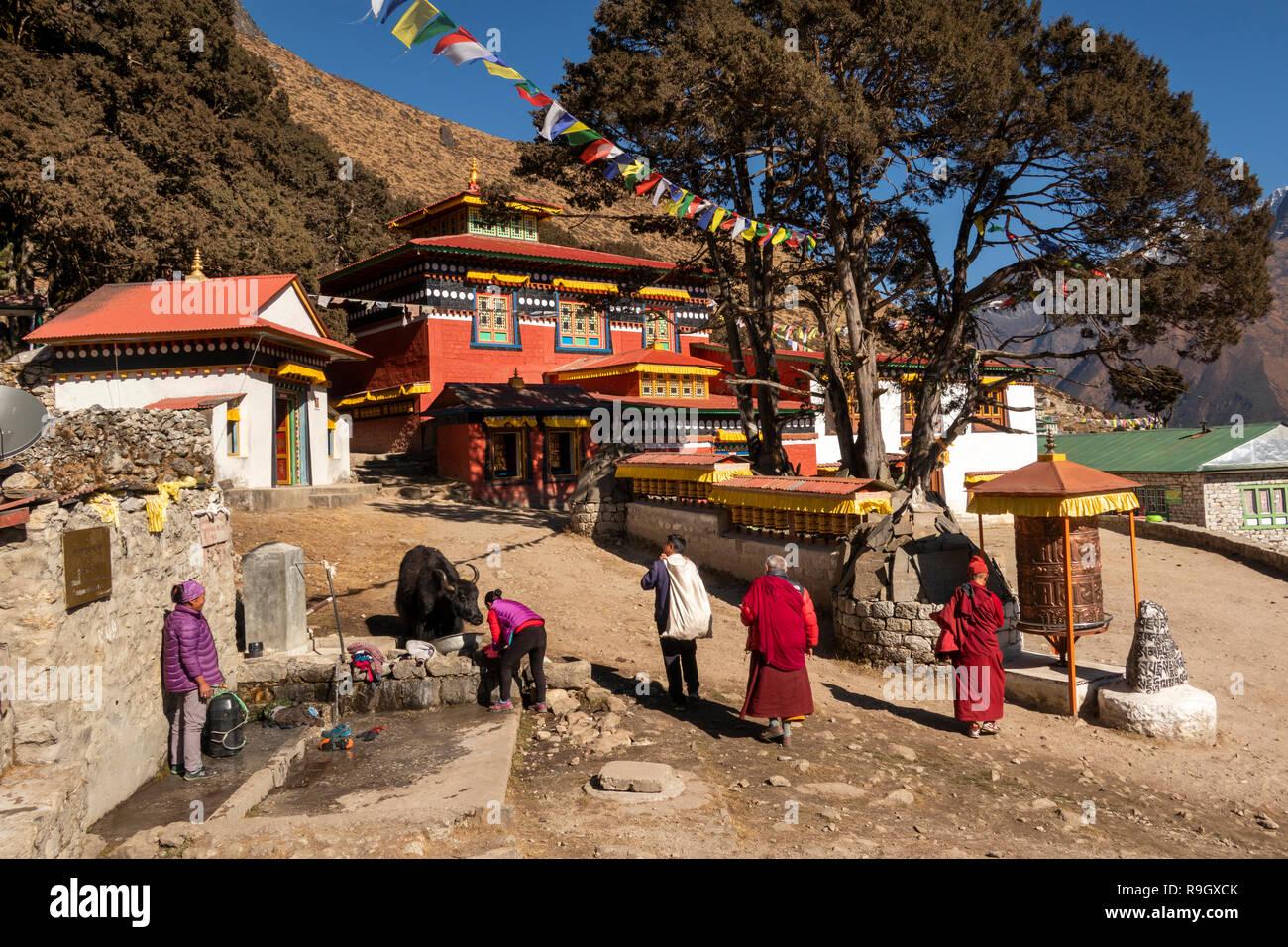 Nepal, Everest Base Camp Trek, Khumjung, monks passing traditional prayer wheels and mani stones outside village gompa - Stock Image
