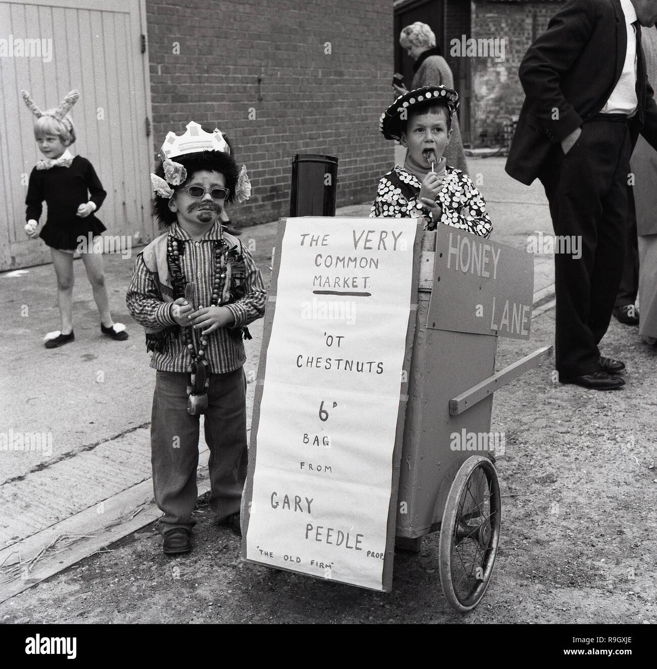 1967, historcial, two young boys in fancy dress costume - one as an East End of London Pearly King - selling chestnuts at 6D a bag from their small homemade cart in the street at the  Prestwood village fete. Stock Photo
