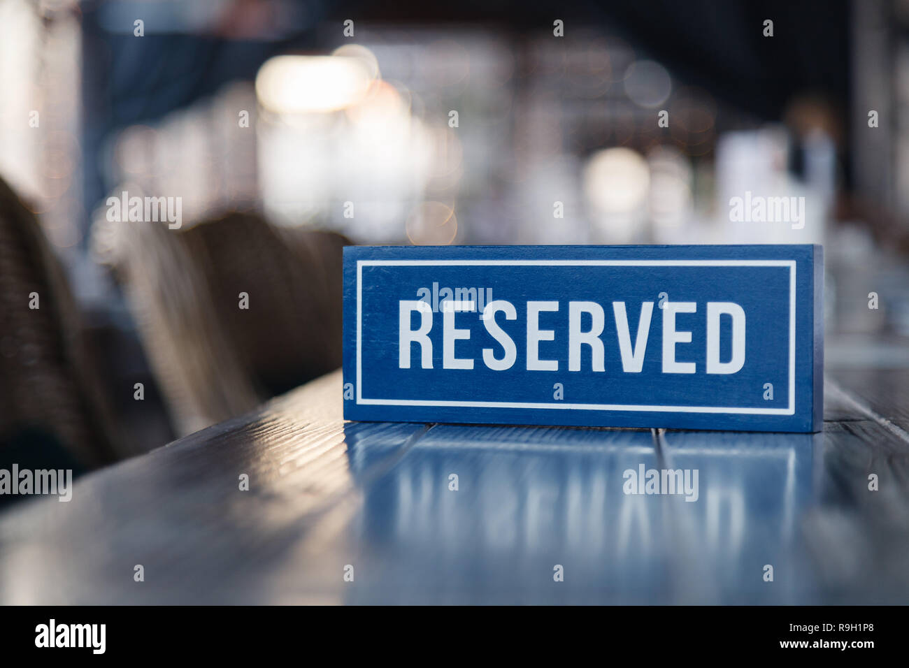 Closeup wooden blue white rectangular plate with the word Reserved standing on gray table in restaurant. Сoncept of preparation for the banquet, close - Stock Image
