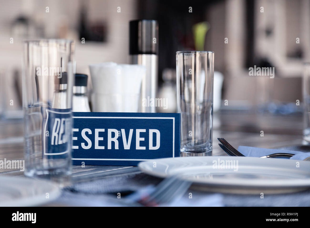 Closeup wooden blue white rectangular plate with word Reserved standing on gray vintage table in restaurant near to the serving, white paper napkins,  - Stock Image