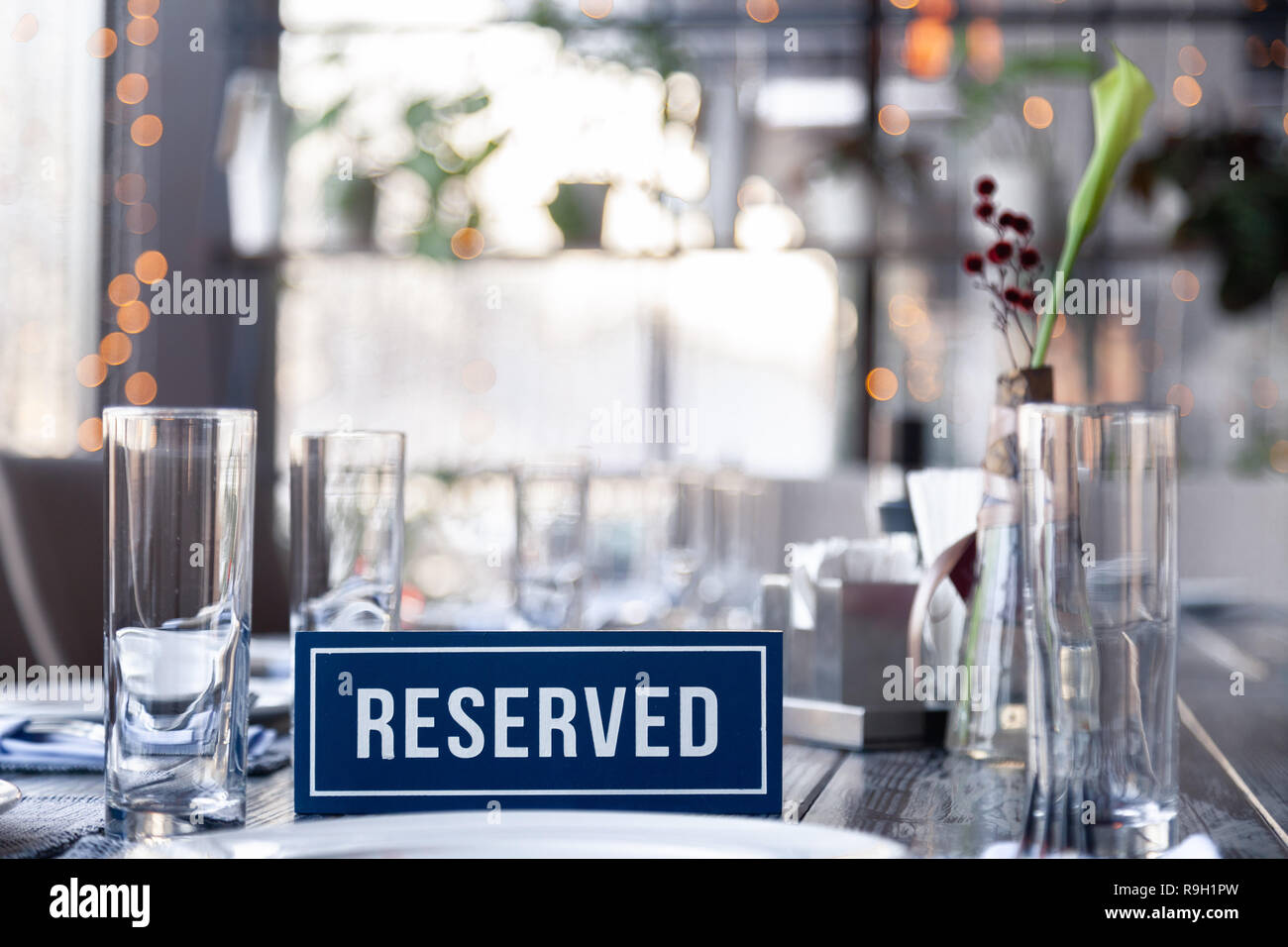 Closeup wooden blue white rectangular plate with the word Reserved standing on gray vintage table in restaurant near to setting, napkins, salt pepper, - Stock Image