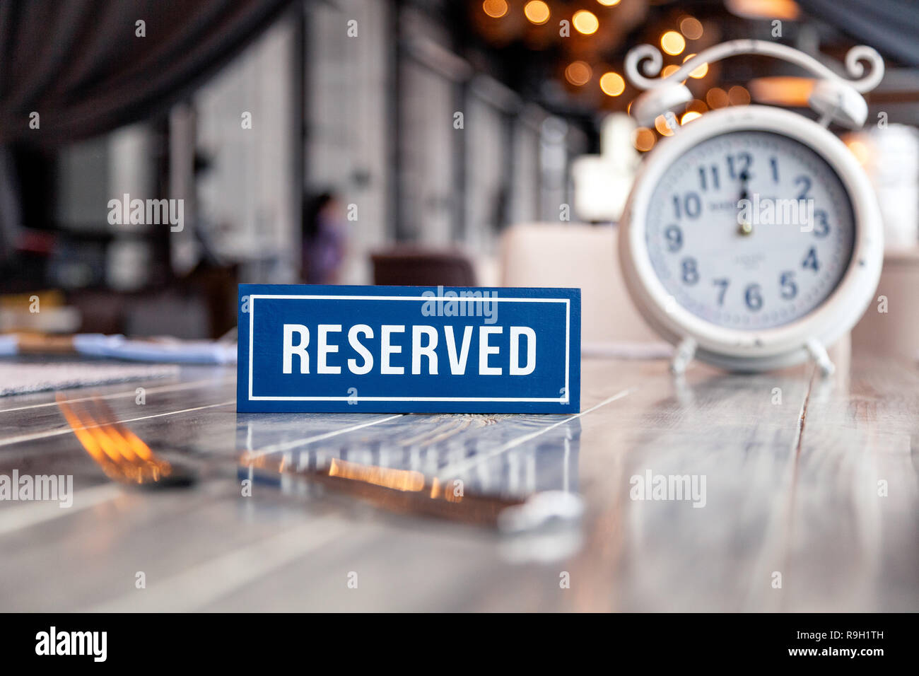 Closeup wooden blue white rectangular plate with the word Reserved standing on gray vintage table in restaurant near to setting, napkins, fork, knife, - Stock Image