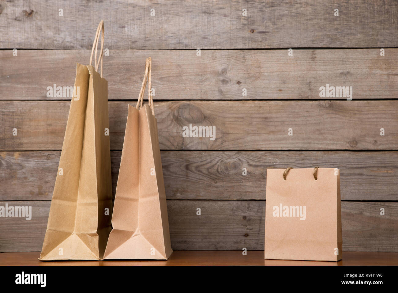 Cardboard shopping bags on wooden background - Stock Image