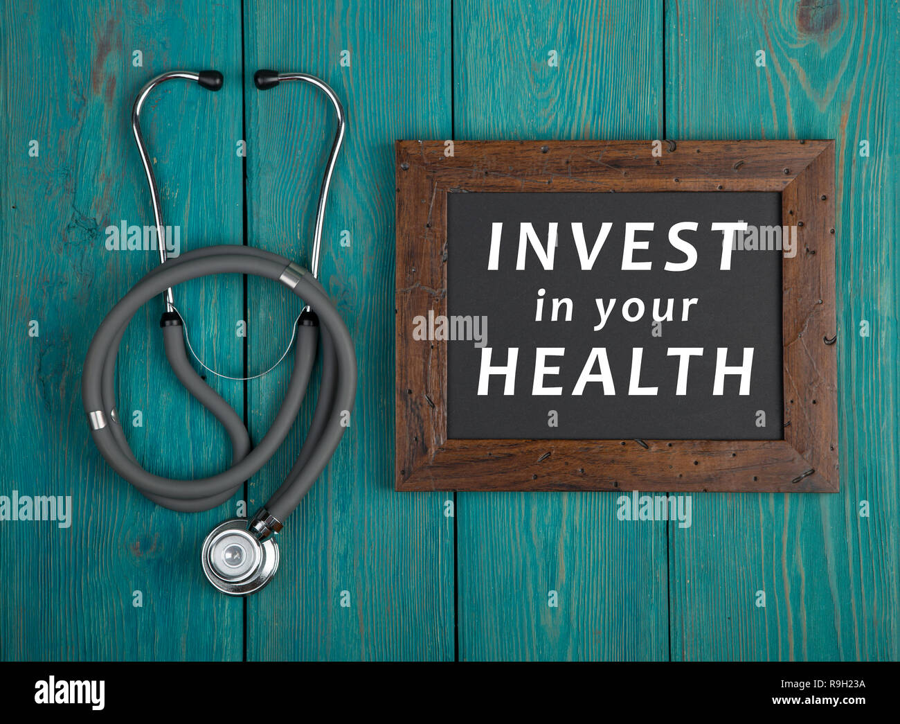 Medecine concept - Blackboard with text 'Invest in your health' and stethoscope on blue wooden background - Stock Image