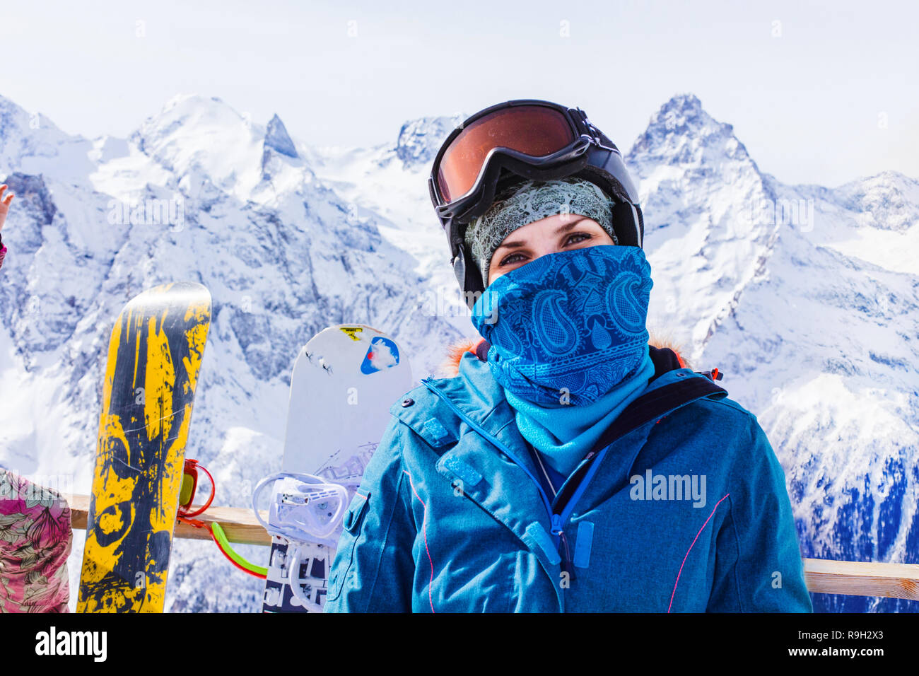 Woman with ski mask on the background of a snowboard and snow-capped  mountains enjoying a sunny winter day. The concept of travel is a way of  life 857ae7177