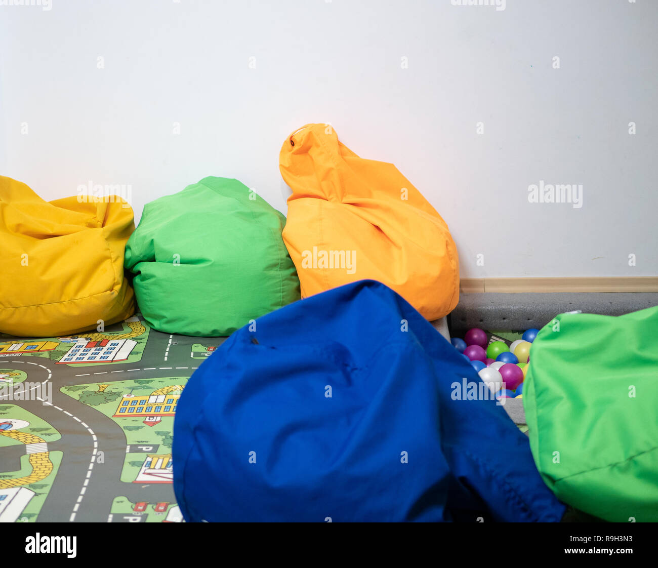 lot of vivid vibrant bean bags at kids playground zone at kindergarten, indoor image with lot of copy space on white background wall - Stock Image