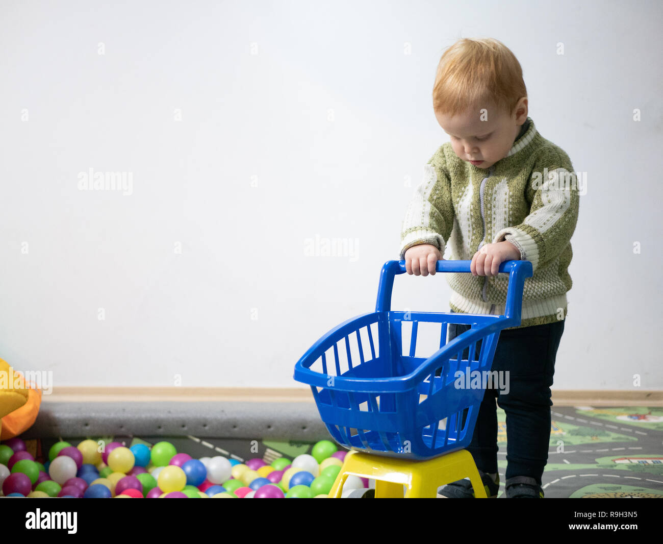 cute adorable 2 year old white caucasian boy playing with shopping cart at privat kindergarten indoor playground - Stock Image