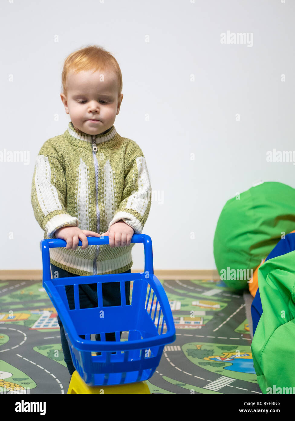 cute little boy holding toy shopping cart at indoor playground room. privat preschool kindergarten concept - Stock Image