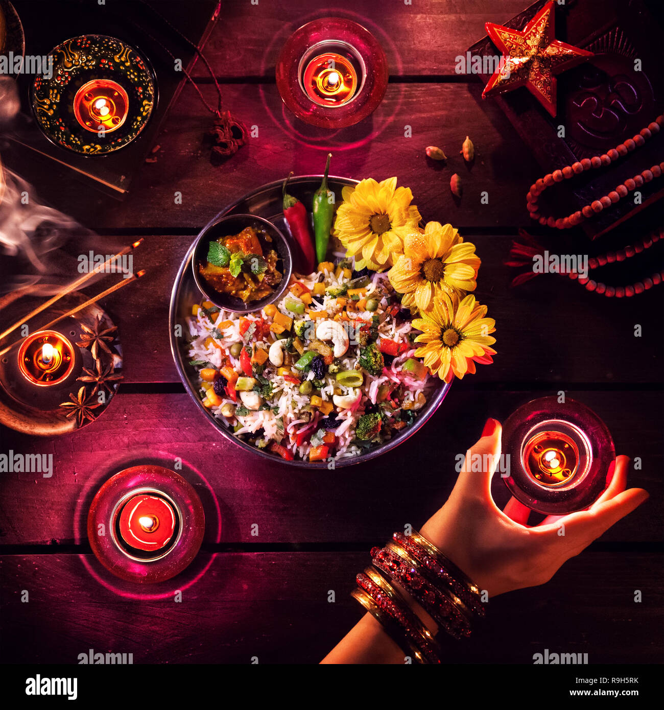 Vegetarian biryani, candles, incense and religious symbols at Diwali celebration on the table - Stock Image