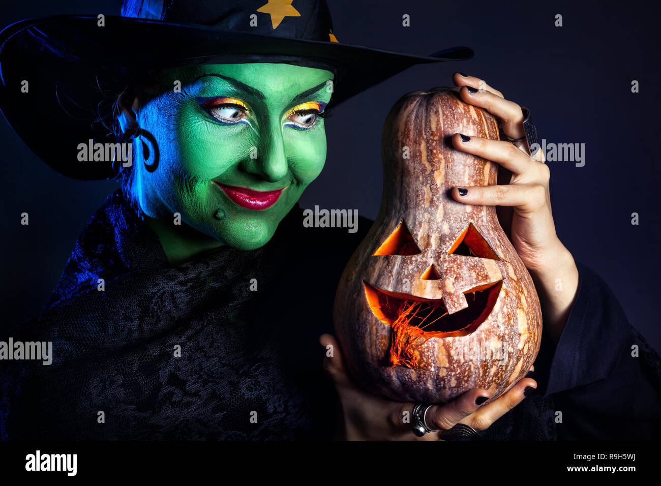 Witch with green skin holding carved Halloween pumpkin at dark background Stock Photo